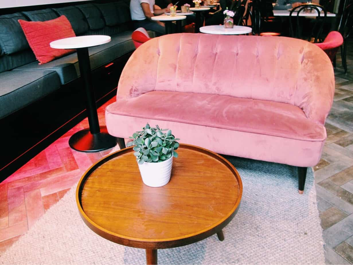 Pink velvet sofa at The Fix, the cafe at the entrance to Ecomama. The cheapest hotel for an instagram- and eco-friendly stay in Amsterdam: Ecomama Hotel Amsterdam is cozy, sustainable and made my time in Amsterdam special.