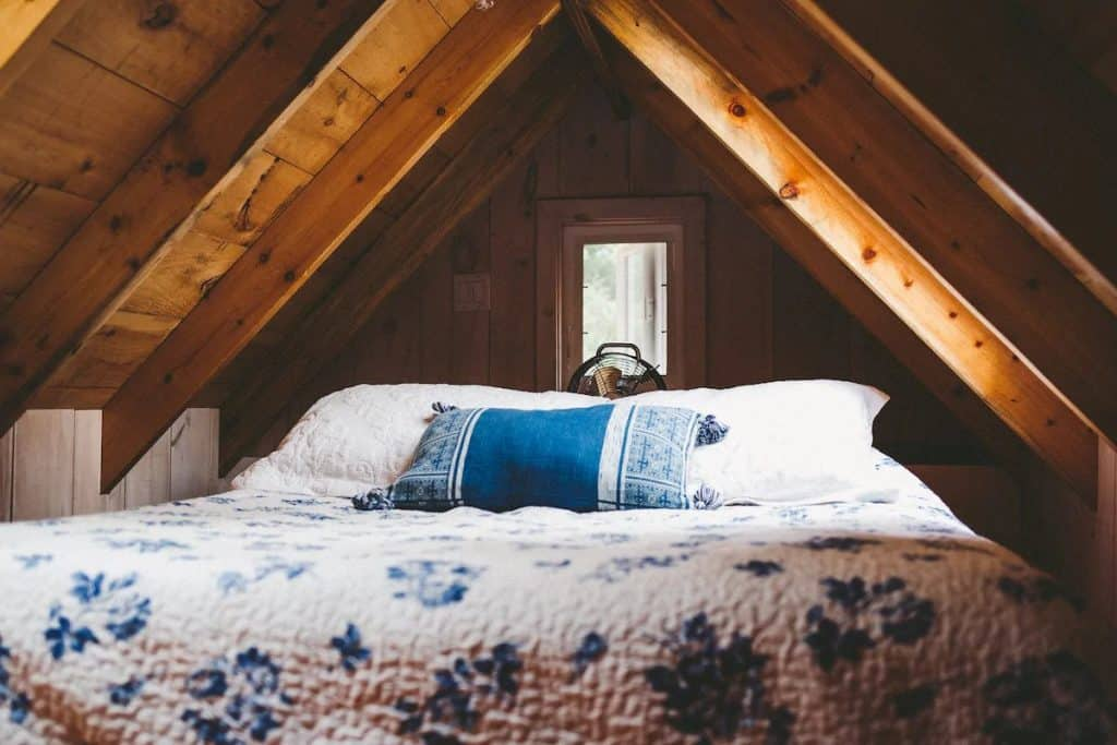 Mattress covered in blue and white quilt in an A-frame cabin loft.