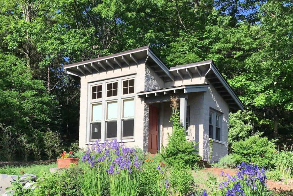 A stone tiny house in a flower garden.
