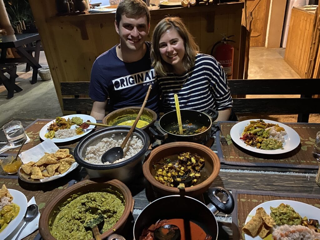 Dan and Sarah sitting in front of the curries they made in Sri Lanka