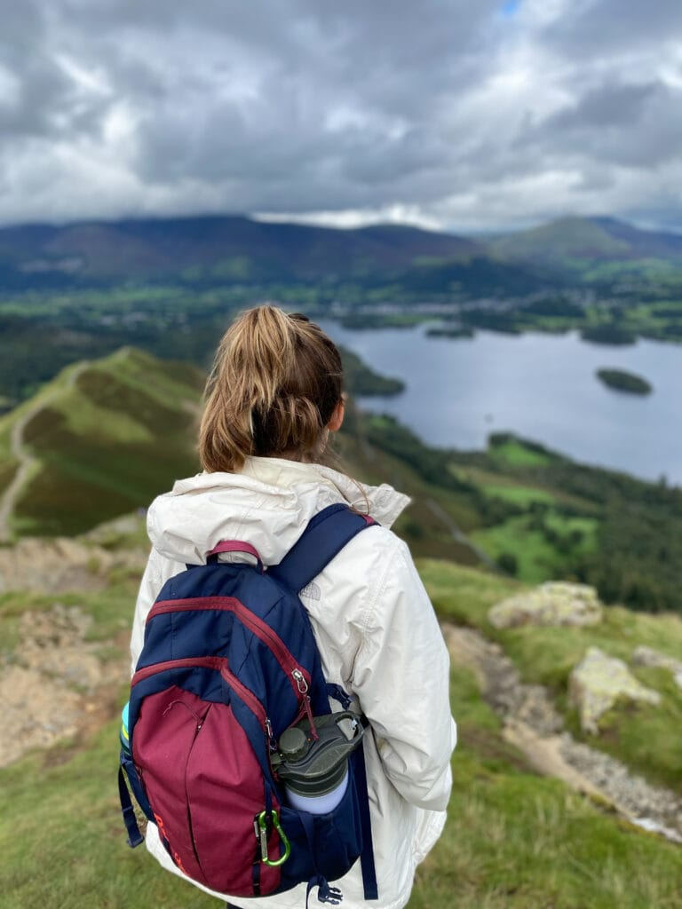 sarah standing with red and blue backpack overlooking keswick - keswick walks